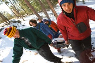 first aid participants carrying a stretcher in the woods