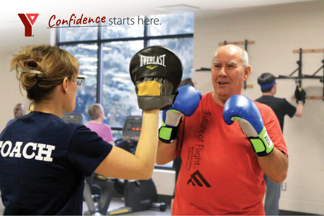 A Rock Steady boxer is improving his balance and eye hand coordination with the help of a coach at the A.R. Kaufman Family YMCA